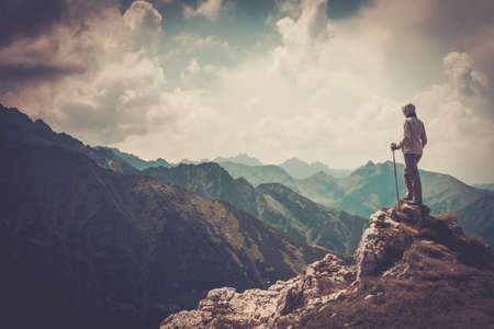 trekking pole: Woman hiker on a top of a mountain