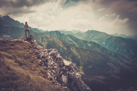 edge of cliff: Woman hiker on a top of a mountain