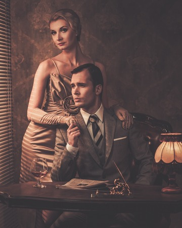 Well-dressed couple sitting behind table photo