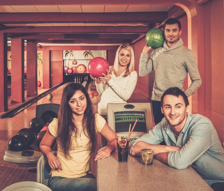 4 people: Group of young people behind table in bowling club Stock Photo