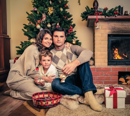 men socks: Family near fireplace in Christmas decorated house interior Stock Photo