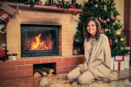 home decorated: Young woman near fireplace in Christmas decorated house interior Stock Photo