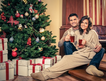 Couple with cups of hot drink near Christmas tree photo