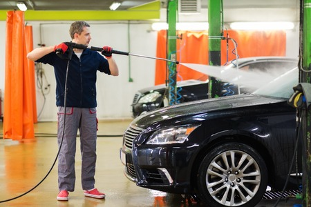 Man worker washing luxury car on a car wash photo