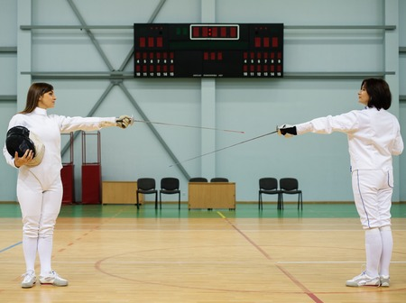 fencing sword: Young woman fencer and her trainer