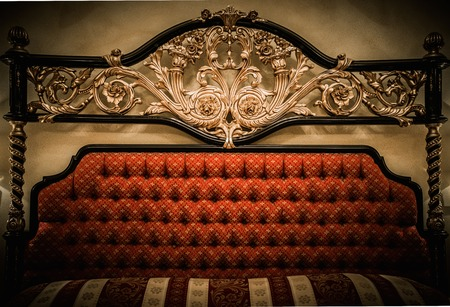 Back of expensive bed with golden ornament photo