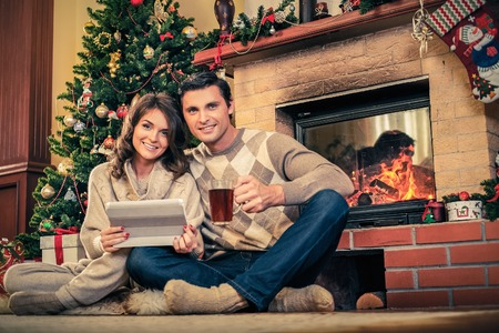 Couple near fireplace in Christmas decorated house with tablet pc photo