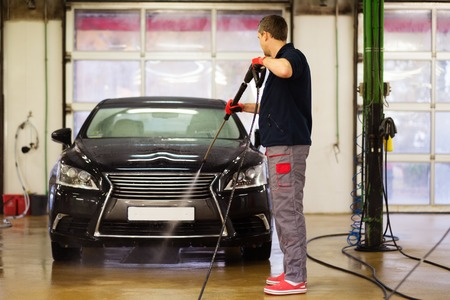 car in garage: Man worker washing luxury car on a car wash