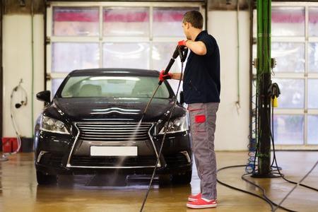 Muž pracovník mytí luxusní vůz na mytí auta