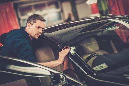 autolavaggio: L'uomo lavoratore lucidatura auto su un autolavaggio Archivio Fotografico