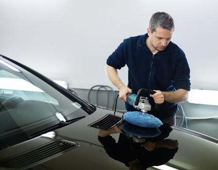 Homem em uma lavagem de carro carro polimento com uma máquina polonês Imagens