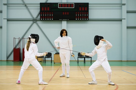 fencing sword: Children fencers and their  trainer