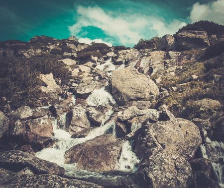 Stream running through rocks in a mountains photo