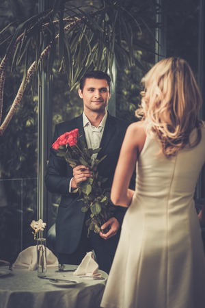 young couple smiling: Handsome man with bunch of red roses dating his lady