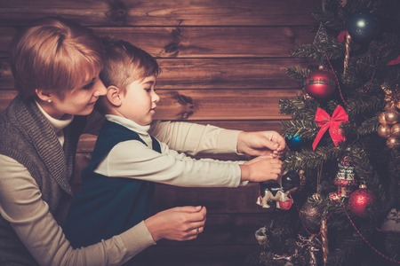 christmas house: Happy mother and her lIttle boy decorating christmas tree in wooden house interior