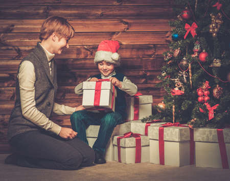 miracle tree: Mother and lIttle boy with gift box under christmas tree in wooden house interior Stock Photo
