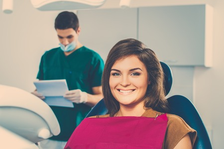 hygienist: Man dentist reading woman patients card Stock Photo