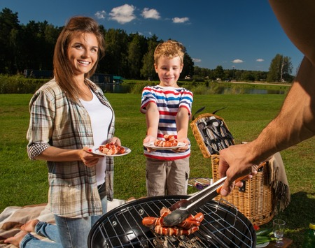 Young family preparing sausages on a grill outdoors photo