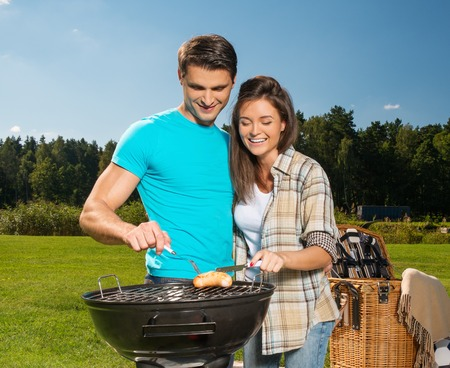 Young couple preparing sausages on a grill outdoors photo