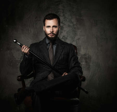 man in chair: Handsome well-dressed man with walking stick sitting in leather chair