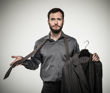 menswear: Handsome man with beard choosing tie Stock Photo