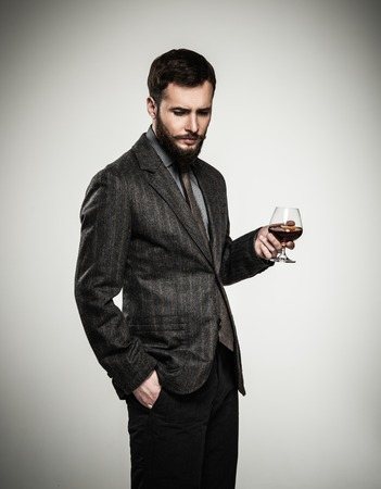 Handsome well-dressed man in jacket with glass of beverage Stock Photo