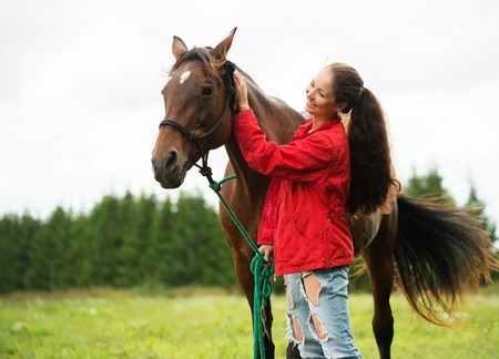 red horse: Beautiful smiling girl with her brown horse outdoors