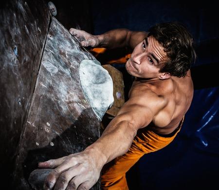 rock climbing man: Muscular man practicing rock-climbing on a rock wall indoors Stock Photo