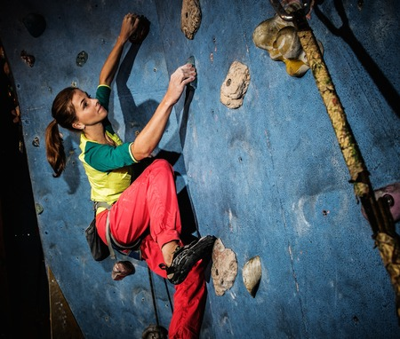 rock climbing: Young woman practicing rock-climbing on a rock wall indoors Stock Photo