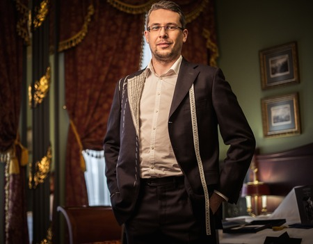 made to measure: Middle-aged man trying on custom made suit in luxury vintage interior