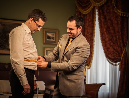 tailored: Tailor measuring client for custom made suit tailoring
