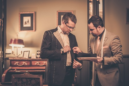bespoke: Tailor and client choosing cloth and buttons for custom made suit Stock Photo
