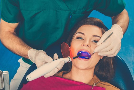Young beautiful brunette woman at dentists surgery photo