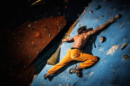 indoors: Muscular man practicing rock-climbing on a rock wall indoors Stock Photo
