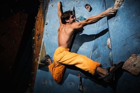 hang up: Muscular man practicing rock-climbing on a rock wall indoors Stock Photo