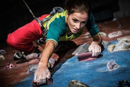 indoors: Young woman practicing rock-climbing on a rock wall indoors Stock Photo