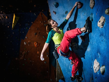 climbing wall: Young woman practicing rock-climbing on a rock wall indoors Stock Photo