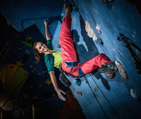boulder: Young woman practicing rock-climbing on a rock wall indoors Stock Photo