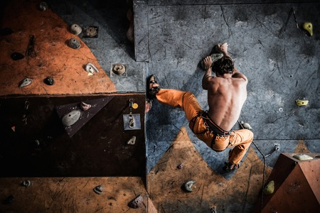Muscular man practicing rock-climbing on a rock wall indoors photo