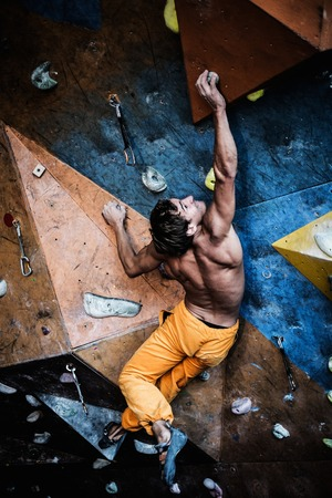Muscular man practicing rock-climbing on a rock wall indoors Stock Photo