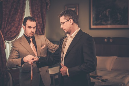 custom made: Tailor measuring client for custom made suit tailoring