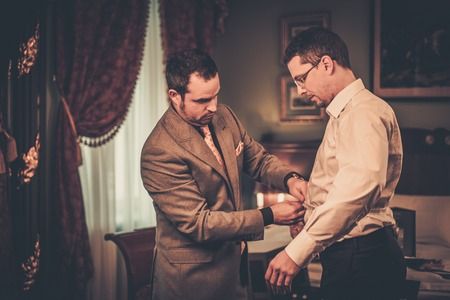 bespoke: Tailor measuring client for custom made suit tailoring