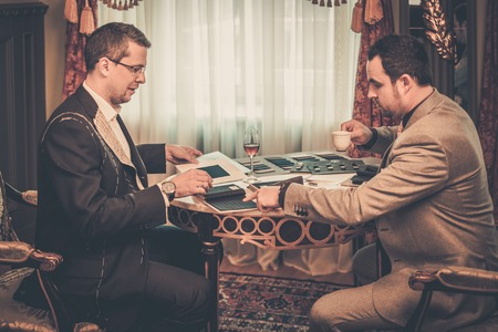 tailored: Tailor and client choosing cloth and buttons for custom made suit Stock Photo