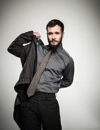 put: Handsome man with beard putting on jacket Stock Photo