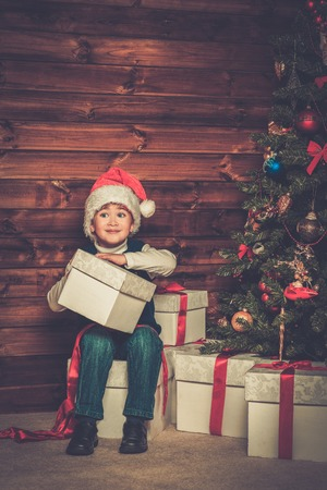 miracle tree: Little boy with gift box under christmas tree in wooden house interior