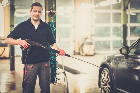 Man worker washing luxury car on a car wash photo