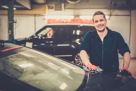 Cheerful worker wiping car on a car wash photo