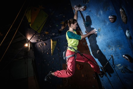 Young woman practicing rock-climbing on a rock wall indoors photo