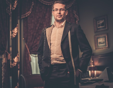 tailored: Middle-aged man trying on custom made suit in luxury vintage interior