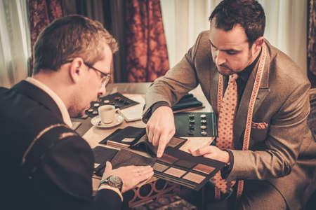 tailor shop: Tailor and client choosing cloth and buttons for custom made suit Stock Photo